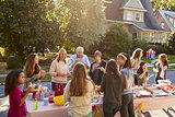 Neighbours talk and eat around a table at a block party