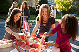 Girls helping themselves to watermelon at a block party