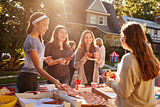 Teen girls eating pizza and talking at a block party