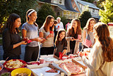 Group of teen girls talking over food table at a block party