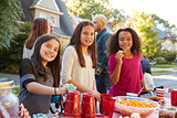 Pre-teen girls smiling to camera at a block party, close up