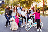 Group of kids with dog smile to camera in a residential street