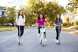 Three pre-teen girls on scooters and bike looking to camera