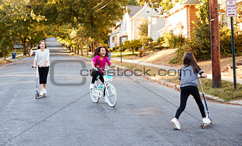 Three girls riding on scooters and a bike in the street