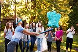 Friends watch teenage girl hitting a pi–ata on her birthday