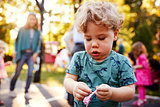 Toddler boy unwrapping a lollipop outdoors