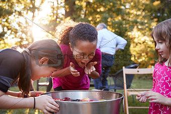 Three young girls apple bobbing at a backyard party