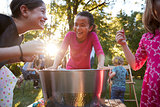 Three young girls have fun apple bobbing at a backyard party