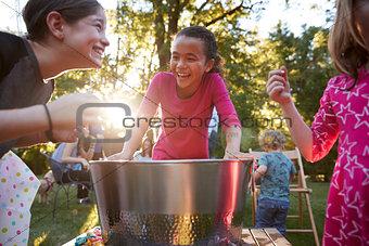 Three young girls have fun apple bobbing at a backyard party
