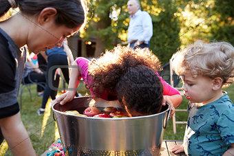 Friends watch pre-teen girl apple bobbing at backyard party