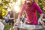 Pre-teen girl apple bobbing, with apple in mouth, close up