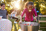 Pre-teen girl, apple in mouth, apple bobbing at garden party