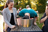 Friends watch teenage boy apple bobbing at a garden party