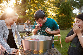 Friends watch teenage boy apple bobbing at garden party