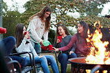 Teenager pours drinks for girlfriends sitting round firepit