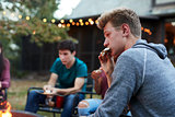 Teenage boy eating sÕmore with friends at a fire pit