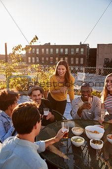 Friends talking at a party on a rooftop, vertical