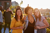 Female friends at a rooftop party smiling to camera