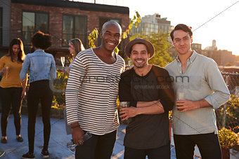 Three male friends at a rooftop party smiling to camera