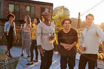 Three male friends laughing and drinking at a rooftop party