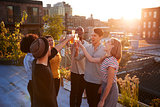 Friends make a toast at a rooftop party, backlit by sunlight
