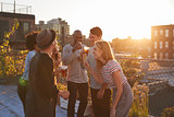 Friends stand talking at rooftop party, backlit by sunlight