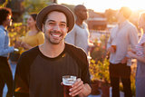 Young man at a rooftop party smiling to camera