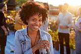 Young black woman at a rooftop party smiling to camera