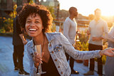 Young woman dancing at a rooftop party smiling to camera