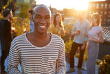 Young black man at a rooftop party smiling to camera