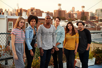 Six adult friends standing together on a Brooklyn rooftop