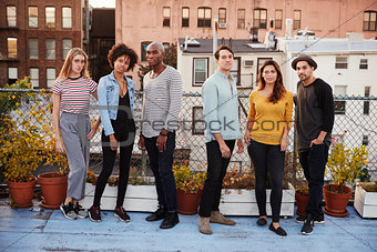 Six adult friends standing together on rooftop, full length