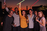 Adult friends waving glowsticks at rooftop party in Brooklyn
