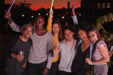 Happy friends waving glowsticks at rooftop party in Brooklyn