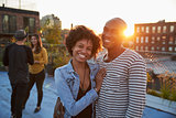Young black couple embracing at a rooftop party