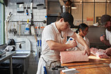 Three butchers preparing meat,cuts of meat at a butcher's shop