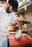 Man in butcher's shop preparing food for customer, vertical