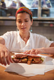 Young woman wrapping a sandwich at a deli counter, vertical