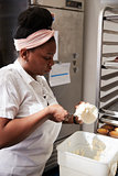 Young black woman at a bakery preparing cake frosting