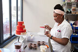 Young black woman frosting cakes at a bakery