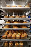 Stacked baking trays of freshly baked muffins at a bakery