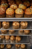Stacked baking trays of fresh muffins at a bakery, close up