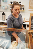 Young woman arranging the confectionary counter at a bakery