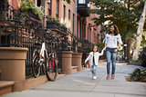 Mother and daughter walking down the street