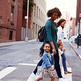 Two mother friends with daughters crossing road, close up
