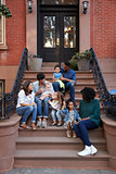 Two families with kids sitting on front stoops, vertical
