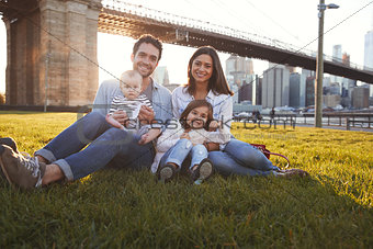 Young family with two daughters sitting on lawn, close up