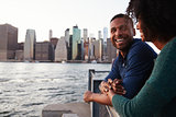 Young black couple standing on quayside, side view