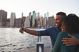 Young black couple taking photo on quayside, side view