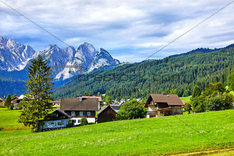 Austrian village among green meadows and Alps